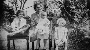 Eine alte Frau mit drei kleinen Kindern sitzt auf einer Bank.